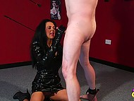 Slut in a vinyl suit has managed to chain a man up and now she is going to give him a handjob