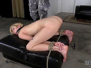 Tied up blonde has to stay in doggystyle, but the man in gas mask masturbates her pussy