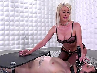 Blonde in black lingerie and stockings tramples slave's cock using heavy sole after handjob