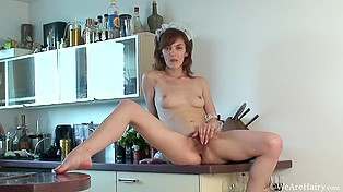 Excited housemaid with cute face climbs the kitchen countertop to masturbate hairy pussy
