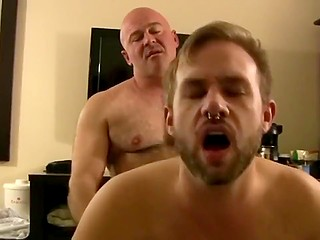Older gay with muscular body fucks the bearded possessor of nose piercing on the bed